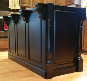 custom island by ryan bruzan in louisville, kentucky. the island features raised panel assembly, decorative legs and corbels, and is spray painted black satin lacquer