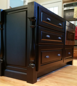 custom black island by ryan bruzan in louisville, kentucky. the island features raised panel assembly, decorative legs and corbels, and is spray painted black satin lacquer