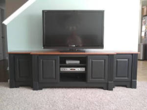 black entertainment console with fluted columns, raised panel doors, concealed hinges and stained oak countertop